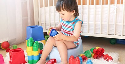 Potty training toddler playing with blocks